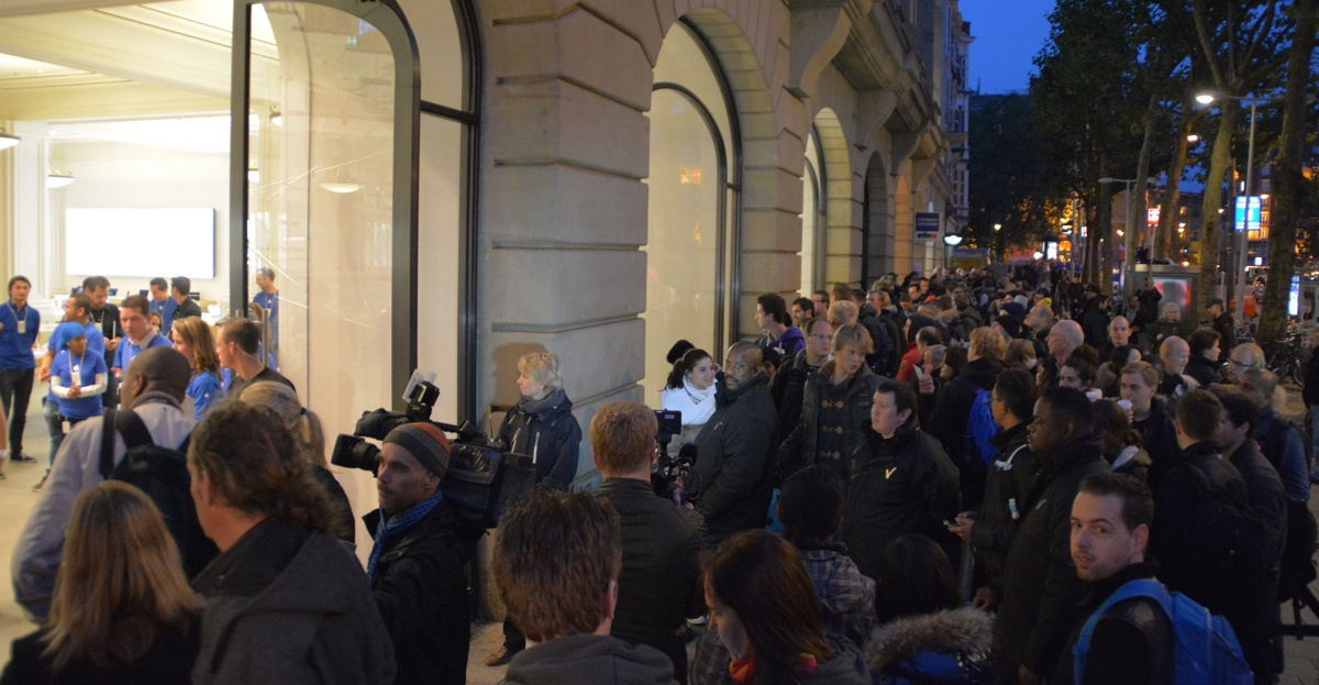 Line of people waiting to get into an Apple store.